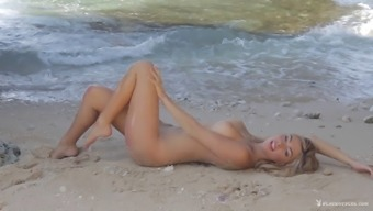 Beautiful tattooed blonde stripping and posing at the beach