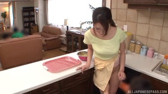 Topless and busty Japanese girl blows two guys in her kitchen