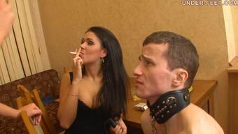 Hot femdom diva in heels smoking while slave licks her foot