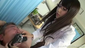Hot Japanese doctor with glasses giving a handjob to her patient