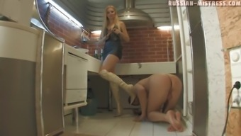 Upbeat foot fetish blonde in high heels riding on her slave in the kitchen