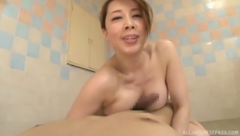 Japanese MILF Yumi Kazama gives a sloppy soapy titjob in the bathroom