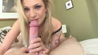 Affectionate tattooed blonde taking a closer look of huge dick before giving out blowjob